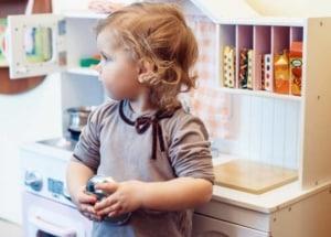 Kind an einer Spielküche aus Holz im Landhausstil (depositphotos.com)